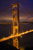 Golden Gate Bridge, Night Vertical with Lights of San Francisco, California in Background Photographic Print by William Perry