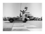 Man jumping waving checkered flag Giclee Print by  H. Armstrong Roberts