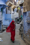 A Woman in a Red Sari Walks Down a Street in Jodhpur's Blue City Photographic Print by Steve Winter