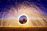 Burning Steel Wool Spinned near the Sea. Showers of Glowing Sparks from Spinning Steel Wool Photographic Print by  Andrius_Saz