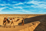 Rajasthan Travel Background - India Cameleer (Camel Driver) with Camels in Dunes of Thar Desert. Ja Photographic Print by DR Travel Photo and Video
