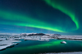 The Northern Lights Dance over the Glacier Lagoon in Iceland. Photographic Print by John A Davis