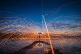 Showers of Hot Glowing Sparks from Spinning Steel Wool on the Rock and Beach Photographic Print by weerasak saeku