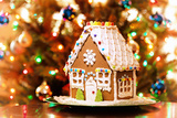 Homemade Christmas Gingerbread House Displayed on a Table. Christmas Tree Lights in the Background. Photographic Print by Leena Robinson