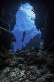 A diver stops at the entrance to an underwater cave in Grand Cayman, Cayman Islands Reproduction photographique par  Stocktrek Images