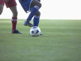 Soccer players from opposing teams compete for the ball during a game Photographic Print