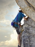 Young man rock climbing up a vertical cliff Photographic Print
