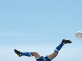 Soccer player upside-down attempting to kick the ball Photographic Print