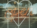 Neon 'Open' sign framed in a heart-shape in a window Fotografiskt tryck