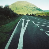 Two painted arrows on a road pointing towards a grassy mountain Photographic Print