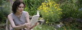 Young Woman Reading a Book in a Garden in a Garden Photographic Print by  Panoramic Images