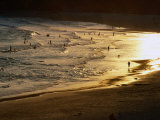 The Setting Sun Illuminates Surfers and Swimmers on Bondi Beach, Sydney, Australia Photographie par Glenn Beanland