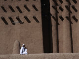 Man Sitting at Base of Mud-Brick Wall of the Grand Mosque, Djenne, Mopti, Mali Photographic Print by Jane Sweeney