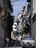 Woman with Baby, Man on Bicycle and Old Car in a Narrow Street Lined with Houses, Havana, Cuba Photographic Print by Rick Gerharter
