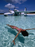 Female Floating in Crystal Waters in Front of Seaplane, Bahamas Photographic Print by Greg Johnston