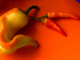 Chilli Peppers in Varying Shades on an Orange Plate, Australia Fotografie-Druck von John Hay