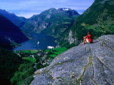 Man Resting on Rock Watching Cruise Ship Sail Out of Geirangerfjord, Geiranger, Norway Photographic Print by Anders Blomqvist