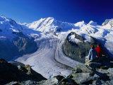Hikers on a Rock at Gornergrat Look Towards Liskamm and the Gorner Glacier, Zermatt, Switzerland Photographic Print by David Tomlinson