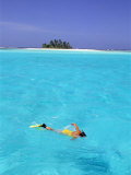 Woman Snorkelling at Sea Surface,Cocos Keeling Island in Background, Indian Ocean, Australia Prints by Jurgen Freund