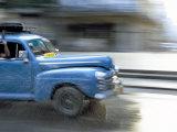 Panned Shot of Old American Car Splashing Through Puddle on Prado, Havana, Cuba, West Indies Photographie par Lee Frost