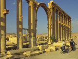 Two Cyclists Pass the Great Colonnade (Cardo), Palmyra, Unesco World Heritage Site, Syria Photographic Print by Eitan Simanor