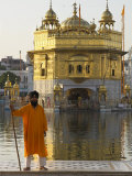 Shrine Guard in Orange Clothes Holding Lance Standing by Pool in Front of the Golden Temple Photographic Print by Eitan Simanor
