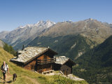 Hiker and Dog on Trail in Front of Traditional Slate Roofed House, Valais, Switzerland Photographic Print by Christian Kober