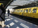 Passengers on the Platform and a Yellow Train, Mendelsshon U-Bahn Station, Berlin, Germany Photographic Print by Richard Nebesky