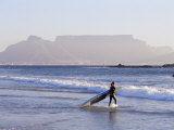 Young Woman Surfer Enters the Water of the Atlantic Ocean with Table Mountain in the Background Photographic Print by Yadid Levy