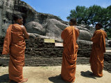 Three Monks in Front of a Statue of the Buddha, Gal Vihara, Polonnaruwa, Sri Lanka Photographic Print by Yadid Levy