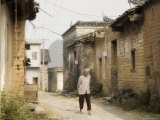 Woman Walking Through Village Streets, Yangshuo, Guangxi Province, China Photographic Print by Jochen Schlenker
