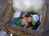 A Small Child Sleeps in a Cart on the Streets of Phnom Penh, Cambodia, Indochina Photographic Print by Andrew Mcconnell