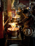 Woman Adding the Melting Yak Butter from Her Lamp to Those of the Temple, Bharkor, Tibet Photographic Print by Don Smith