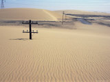 Migrating Barchan Sand Dunes Across Road Marked by Buried Telegraph Poles Photographic Print by Tony Waltham