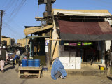 Lady in Burqa Sits on Step Outside Shop, Shor Bazaar, Central Kabul, Afghanistan Photographic Print by Jane Sweeney