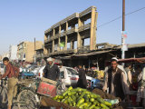 Man Selling Cucumbers from Wheel Barrow in Street Near War Damaged Building, Afghanistan Photographic Print by Jane Sweeney