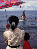 Woman with an Umbrella Watches a Boat Delivering Ashes to the Sea, Bali, Indonesia Photographic Print by Margie Politzer