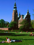 People Relaxing on Lawn with Rosenborg Slot Castle in Background, Copenhagen, Denmark Photographic Print by John Elk III