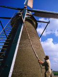 Miller Turning Sails to Stop Windmill in Kinderdijk, Zuid Holland, Netherlands Photographic Print by John Elk III