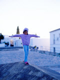Girl Balancing on Edge, Caceres, Extremadura, Spain Photographic Print by Philip & Karen Smith