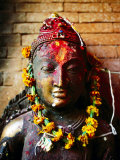 Deity with Garlands and Bindi Powder, Bhaktapur, Bagmati, Nepal Photographic Print by Anthony Plummer