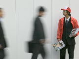 Man Handing Out Coupon Books to Passers-By During Rush Hour at Tokyo Station, Tokyo, Kanto, Japan Photographic Print by Brent Winebrenner