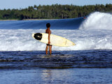 Young Local Boy on Reef Heading out for Afternoon Surf, Lagundri Bay, Indonesia Photographie par Paul Kennedy
