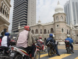 Motorcyclists Wait at Stop Light in Front of Sultan Abdul Samad Building, Kuala Lumpur, Malaysia Photographic Print by Greg Elms