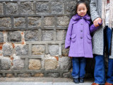 Young Girl Standing Against Stone Wall, Seoul, South Korea Photographic Print by Anthony Plummer
