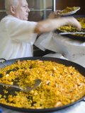 Man Serving Paella, with Noodle Paella in Foreground, Central, Valencia, Spain Photographic Print by Greg Elms