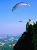 Person Hang-Gliding over Castle with Countryside Beyond, San Marino, San Marino Photographic Print by John Elk III