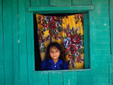 Little Girl in the Window of Her Brightly Painted House, Ciudad Melchor de Mencos, Guatemala Photographie par Jeffrey Becom