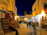 People Strolling along Cobblestone Street Past Carpet Seller at Twilight, Kairouan, Tunisia Photographic Print by Bethune Carmichael