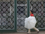 Woman with Umbrella Walking Past Grated House, Bluefields, Atlantico Sur, Nicaragua Photographic Print by Margie Politzer